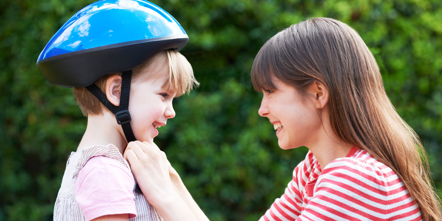 Young Woman Putting Cycle Helmet Onto Girl